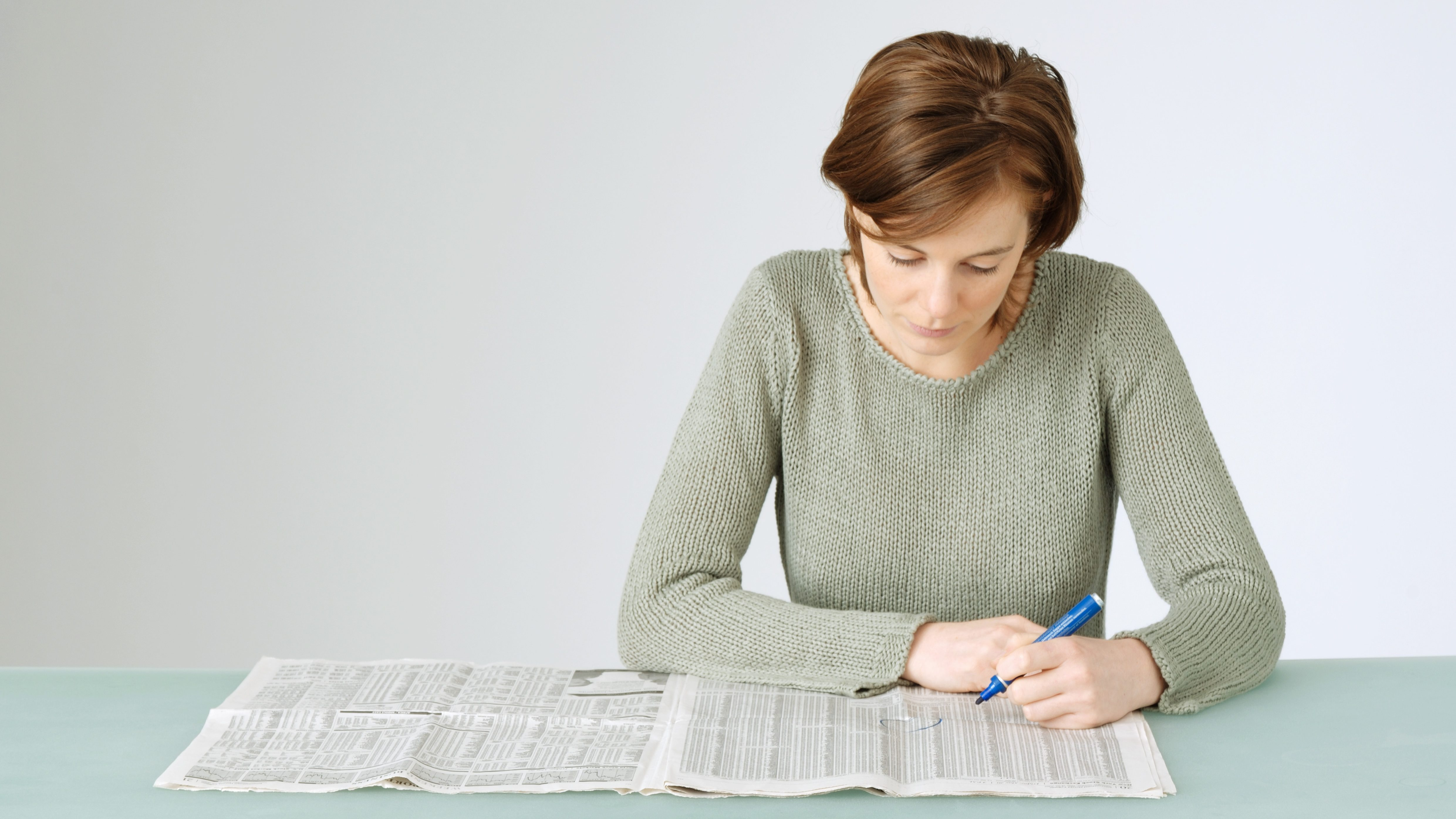 Young woman looking at open newspaper, holding pen