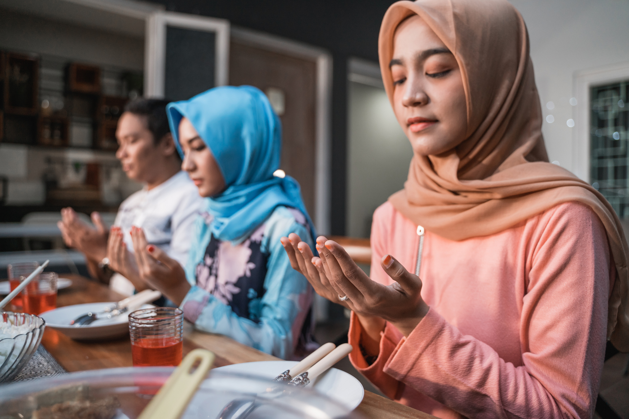 Hijab women and a man pray together before meals, a fast breaking meal served on a table in backyard