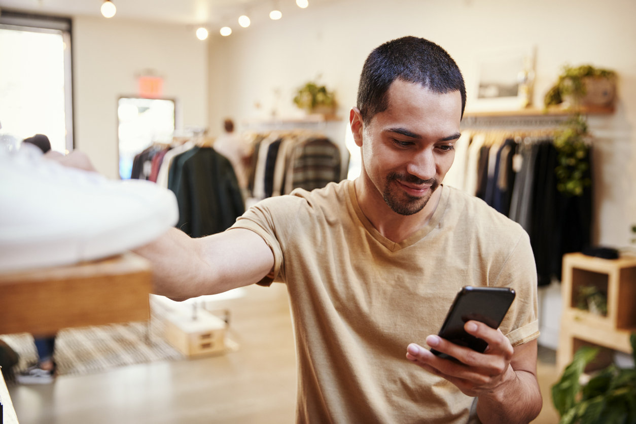 Smiling Hispanic man using smartphone in a clothes shop