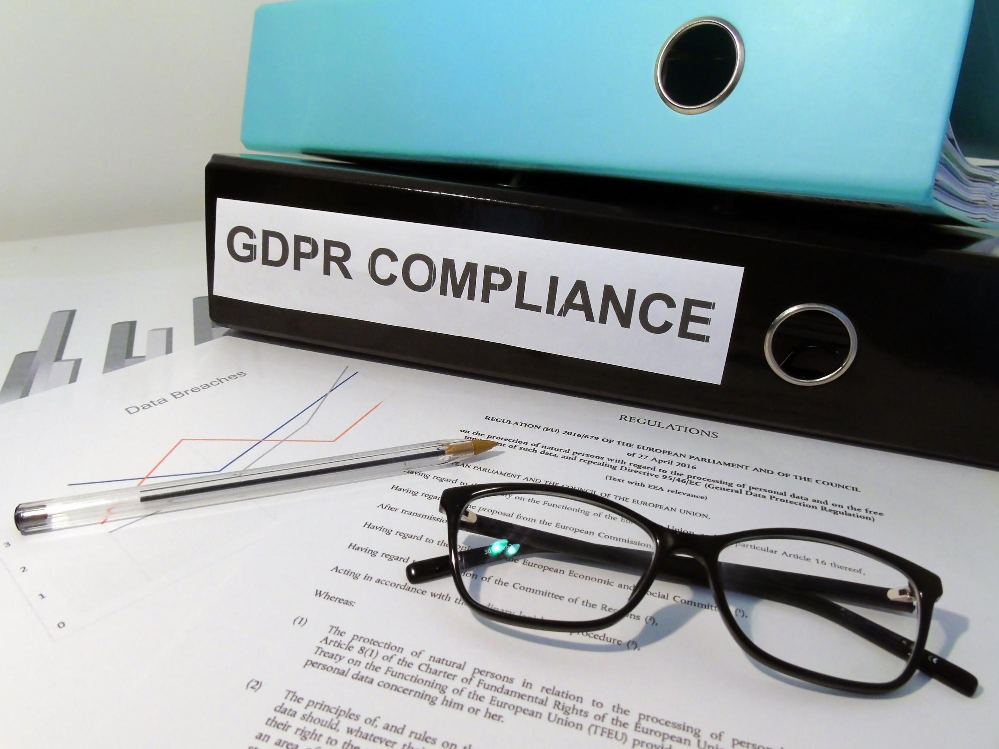 Scene of cluttered desk including folder labelled GDPR Compliance, GDPR legislative text, glasses and pen
