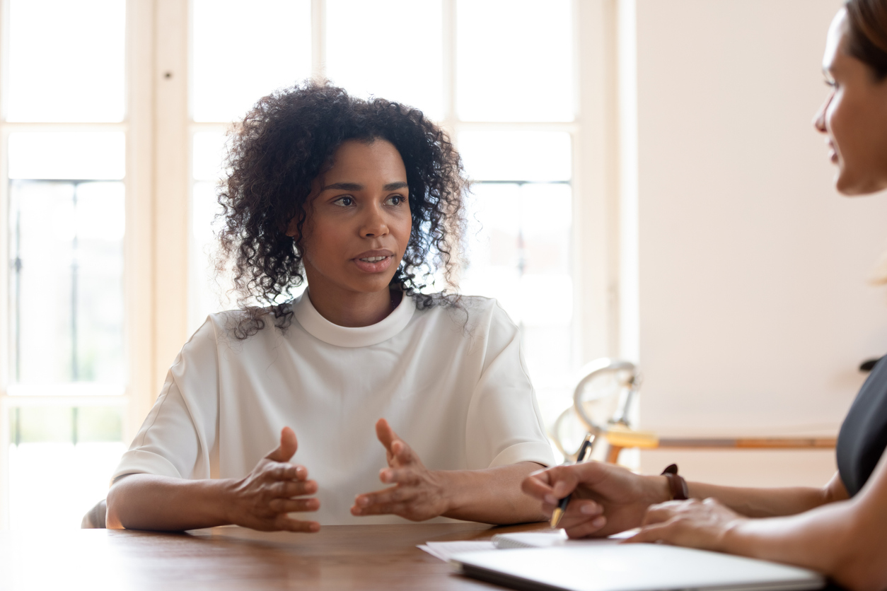 Concentrated African American female job applicant talk at job interview in office, focused confident biracial woman candidate speak negotiate with potential employer, hiring, recruitment concept