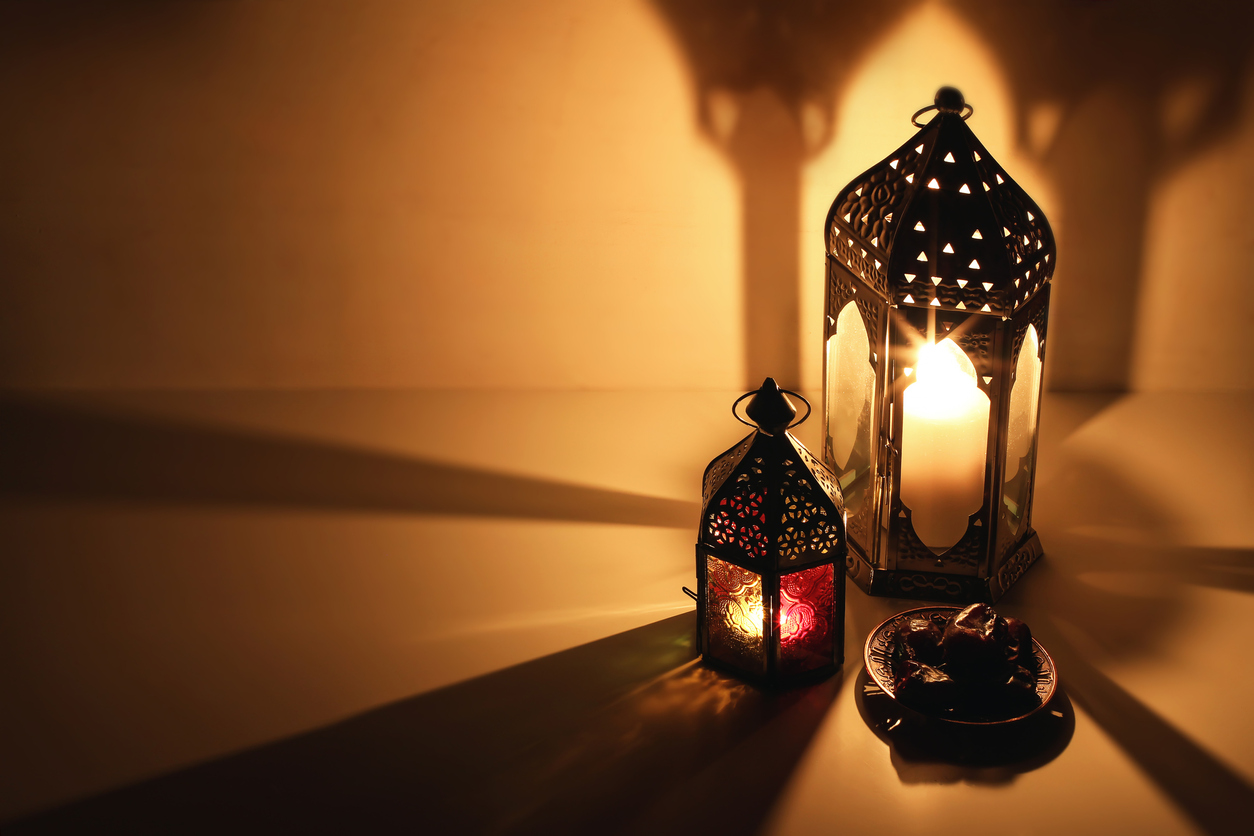 Ornamental Arabic lanterns, burning candles glowing at night. Plate with date fruit on the table. Golden festive greeting card, invitation for Muslim Ramadan Kareem holiday, iftar dinner background.