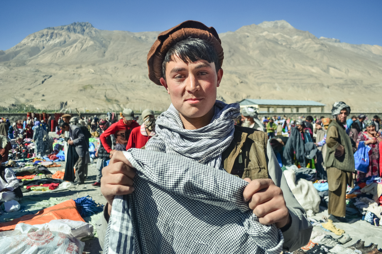 Ishkashim / Afghanistan - October 5, 2013: Handsome Afghan Pashtun young man smiles holding head scarf in Afghan market between Tajikistan and Afghanistan